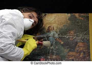 restorer at work on damaged ancient painting