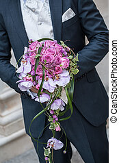 Gay weddings - Groom standing with flowers in the hand, pink...