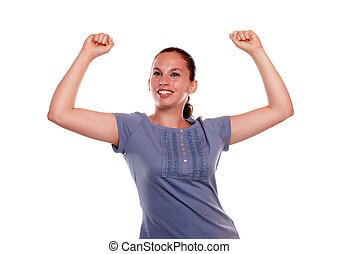Excited young woman smiling with hands up