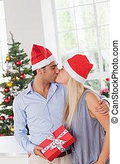 Kissing couple at christmas - Kissing couple wearing santa...