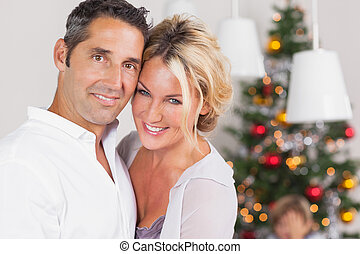 Couple embracing at christmas by dinner table