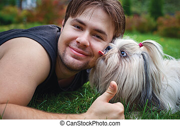 Young man and shih tzu dog portrait.