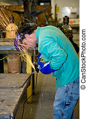 Metal Worker Using Grinder - Metal worker using a grinder to...