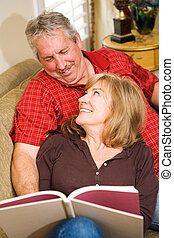 Quality Time - Beautiful mature couple reading together on...