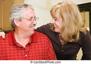 Sharing a Laugh - Happily married mature couple smiling and...