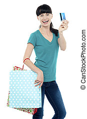 Shopaholic woman holding her cash card up along with polka...