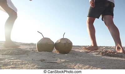 Love concept - Two coconuts placed on sand and couple...