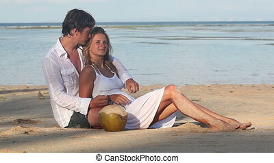 Leisure at beach - Attractive couple with coconuts sitting...