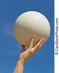 volleyball - white ball in the woman hand against the blue...