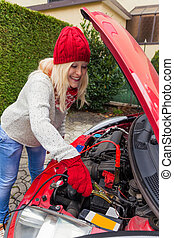 jumper by jumper cables - a young woman starts her car with...