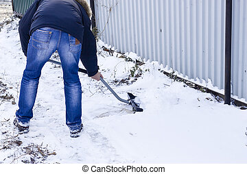 Snow cleaning - The man strenuously cleans snow in a yard