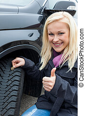 woman measures tire tread of a car tire - a young woman is...