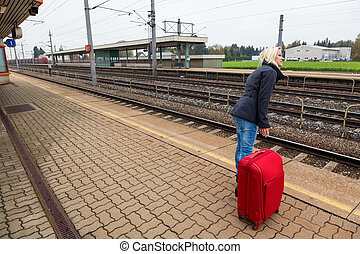 woman waits for her train station - a young woman with...