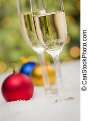 Christmas Ornaments and Champagne Glasses on Snow -...
