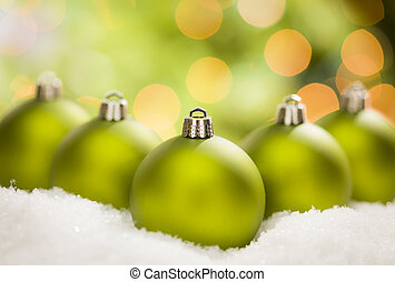 Green Christmas Ornaments on Snow Over an Abstract...