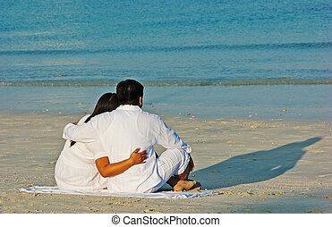 back view of attractive couple sitting on beach and looking