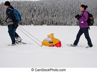 Snoe showing with baby in sled - Snow shoeing across a lake...