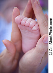 Mother\\\'s love - Mother hold child\\\'s small foot in her...
