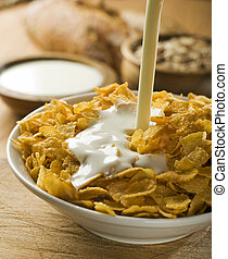 flakes - milk pouring on corn flakes in a bowl