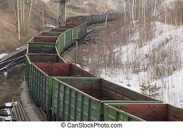Train arrival. - Coal wagons on railway tracks.