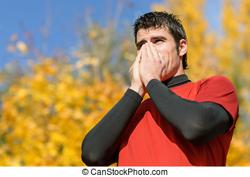 Athlete with cold - Young athlete coughing and blowing with...
