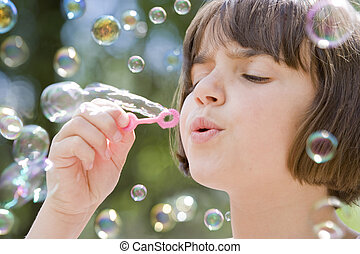 young girl blowing bubbles - young female child blowing a...