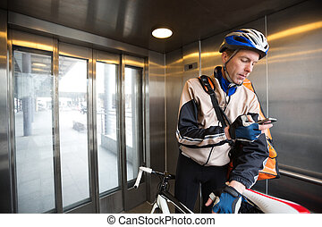 Male Cyclist With Courier Bag Using Mobile Phone In An...