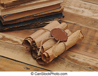 Pile of old books and scroll on wood background