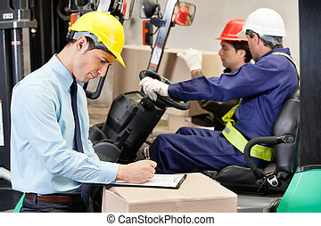 Male Supervisor Writing On Clipboard At Warehouse - Male...