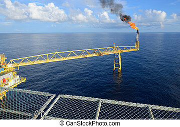 The gas flare is on the oil rig platform