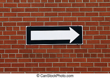 Direction sign on a brick wall pointing to the right