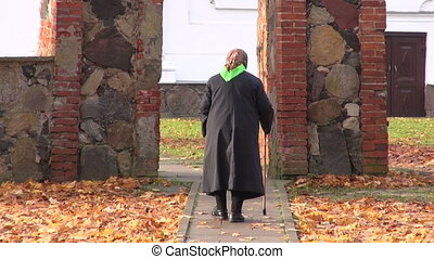 senior woman with stick walking from autumn time church gate
