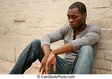 Depressed African American Man Leaning Against Alley Wall -...