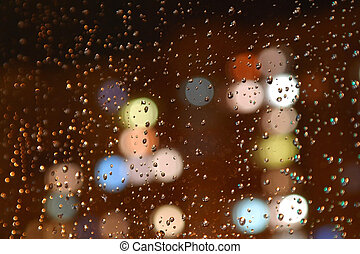 Droplets of night rain on window, on back plan washed away...