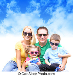 Happy Family in Summer with Clouds - A young happy family is...