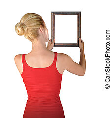 Woman Hanging Blank Art Frame - A young woman is hanging a...