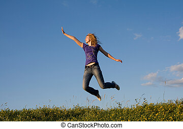 Jumping gir - flying girl on the green meadow