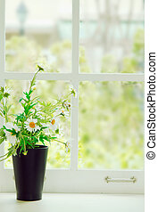 Fresh white flowers in a pot on white retro window sill in...