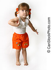 Little girl in an orange shorts wriggles and poses the...