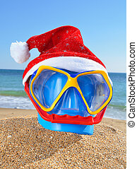 Baby bucket, diving mask and Santas hat on the beach against...