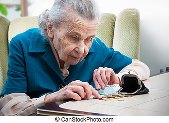 Senior woman counting money - elderly caucasian woman...