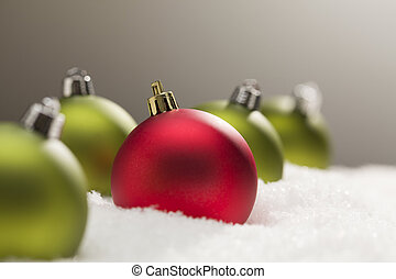 Red and Green Christmas Ornaments on Snow Over Grey