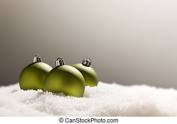Green Christmas Ornaments on Snow Over a Grey Background -...