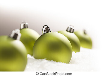 Green Christmas Ornaments on Snow Over a Grey Background