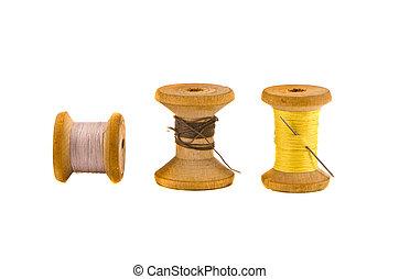 three old thread spools on white