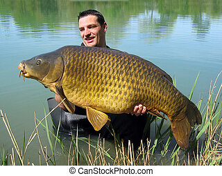 common carp - Happy fisherman holding a giant common carp