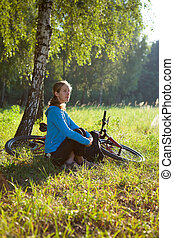 Young cyclist enjoying relaxation in spring in the morning park