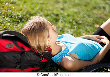 Girl backpacker enjoying relaxation lying in the fresh grass...