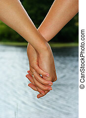 Hand in a hand on a background water