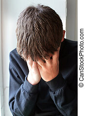 Sorrowful Teenager hide his face